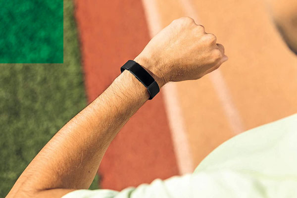 man looking at fitbit on wrist